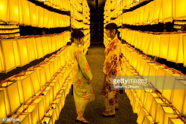 Women wearing kimonos walk through lit paper lanterns during the Mitama Matsuri summer festival at Yasukuni Shrine on July 13 2017 in Tokyo Japan The...