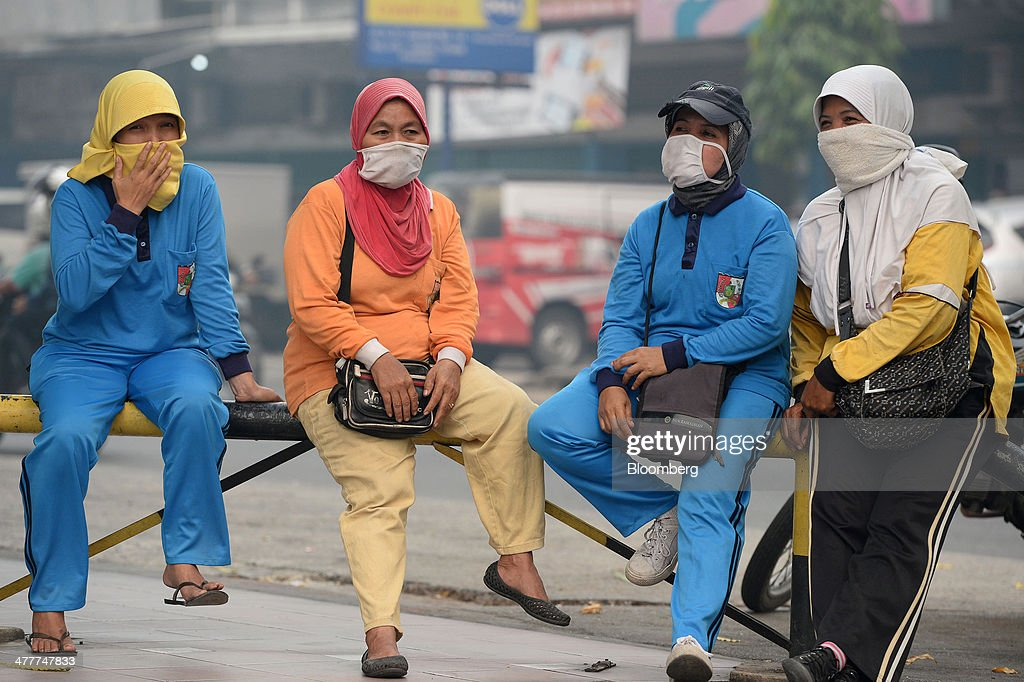 Women wearing masks sit by the side of a road in downtown Pekanbaru, Riau Province, Indonesia on Friday, March 7, 2014. Indonesian central bank Governor Agus Martowardojo embarked on the country's most aggressive rate-increase cycle in eight years within a month of taking the helm in May to shore up the rupiah and damp price pressures. Photographer: Dimas Ardian/Bloomberg via Getty Images