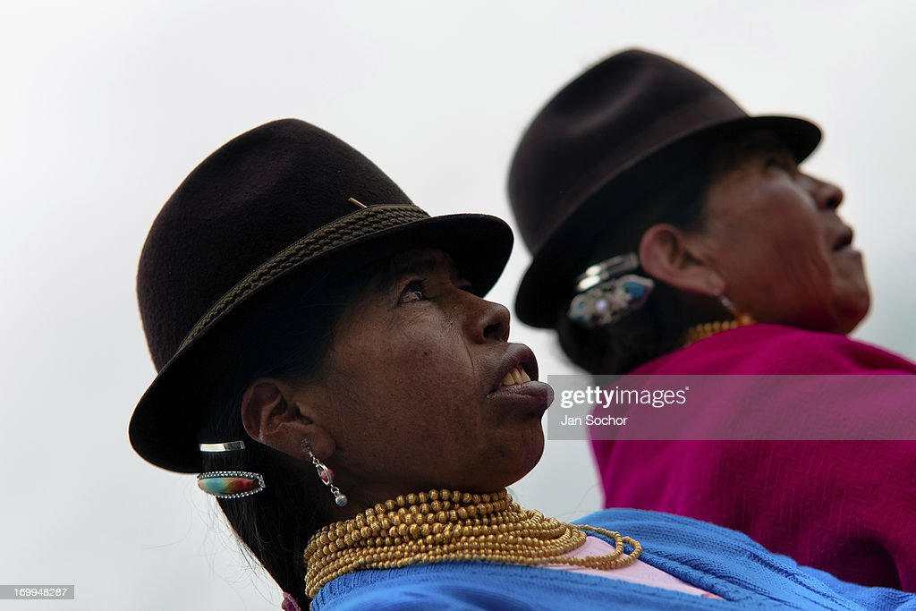 "Women, wearing men's hats, watch a procession during the Inti Raymi celebration on 26 June 2010 in the village of Pesillo, Ecuador. Inti Raymi, ""Festival of the Sun"" in Quechua language, is an ancient spiritual ceremony held in the Indian regions of the Andes, mainly in Ecuador and Peru. The lively celebration, set by the winter solstice, goes on for various days. The highland Indians, wearing beautiful costumes, dance, drink and sing with no rest. Colorful processions in honor of the God Inti (Sun) pass through the mountain villages giving thanks for the harvest and expressing their deep relation to the Mother Earth (Pachamama)."