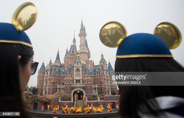 Women wearing Mickey Mouse ears watch the opening ceremony of the Shanghai Disney Resort in Shanghai on June 16 2016 Entertainment giant Disney...
