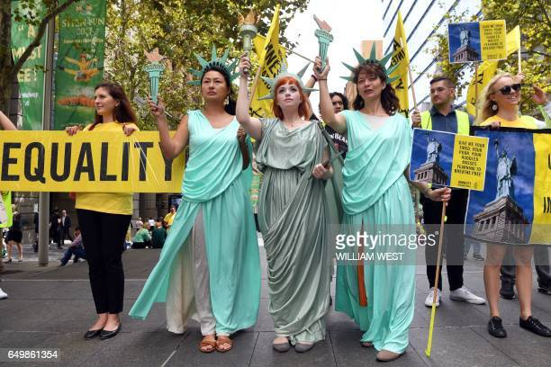 TOPSHOT Women wearing Statue of Liberty costumes protest US President Donald Trump's immigration policies in Sydney's Martin Place on March 9 2017 /...