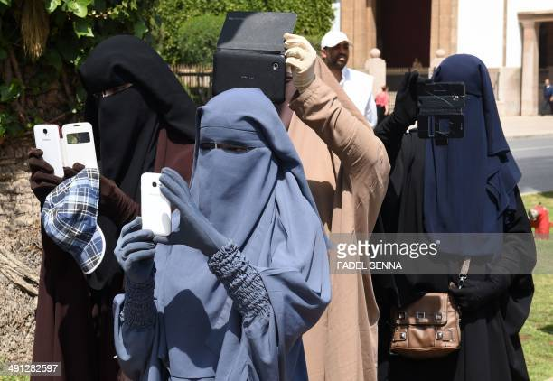 Women wearing the niqab take photos during a demonstration in front of the parliament in Rabat on May 16 the 11th anniversary of the deadly suicide...