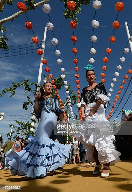 Women wearing the traditional flamenco dresses often in bright colors and accessorized with flower in hair dance around casetas at the 'Feria de...