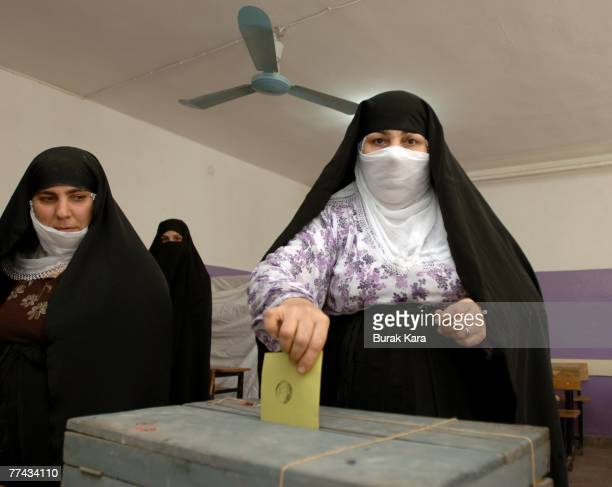 Women wearing traditional black chadors cast their votes during a referendum at a voting centre in a primary school October 21 2007 in Iraqi border...