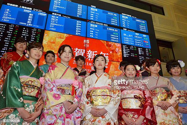 Women wearing traditional kimono dresses pose in front of a quotation board after the opening of the stock market for the new year at the Tokyo Stock...
