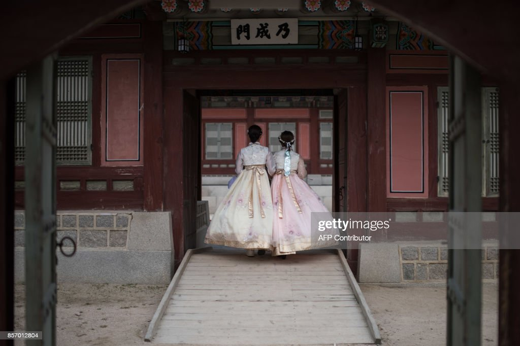 TOPSHOT - Women wearing traditional Korean hanbok dress walk through Gyeongbokgung palace in Seoul on October 3, 2017. South Korea is observing the annual Chusok harvest festival - a week-long holiday during which families typically offer thanks and prayers to their ancestors. / AFP PHOTO / Ed JONES