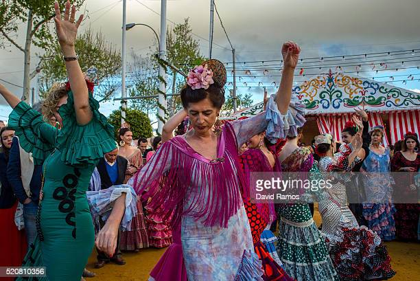 Women wearing traditional Sevillana dresses dance a Sevillana at the Feria de Abril on April 12 2016 in Seville Spain The Feria de Abril has a...