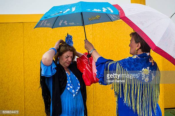 Women wearing traditional Sevillana dresses hold umbrellas as they arrive to the Feria de Abril under a heavy rain on April 12 2016 in Seville Spain...