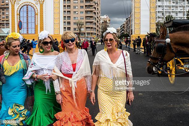 Women wearing traditional Sevillana dresses walk towards the Feria de Abril on April 12 2016 in Seville Spain The Feria de Abril which has a history...
