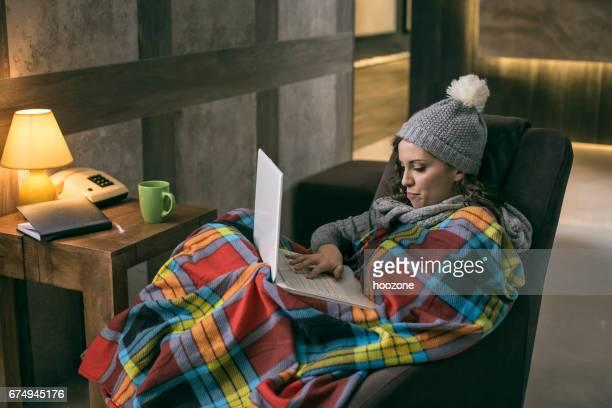 Frauen tragen Winter Mütze arbeiten am Laptop, eingewickelt in eine Decke zu Hause mit keine Heizung