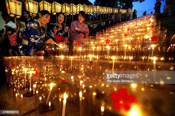 Women wearing yukata Japanese summer kimono lights candles during the MantonoYube or an evening with thousands candles at Hofu Tenmangu Shrine on...