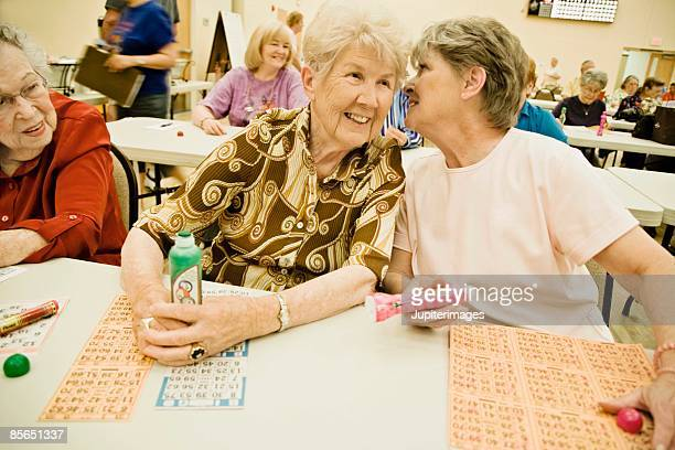 Women whispering and playing bingo