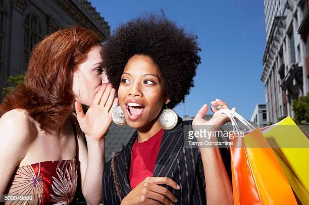 Women whispering on city street