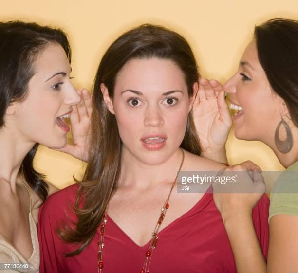 Women whispering secrets to friend