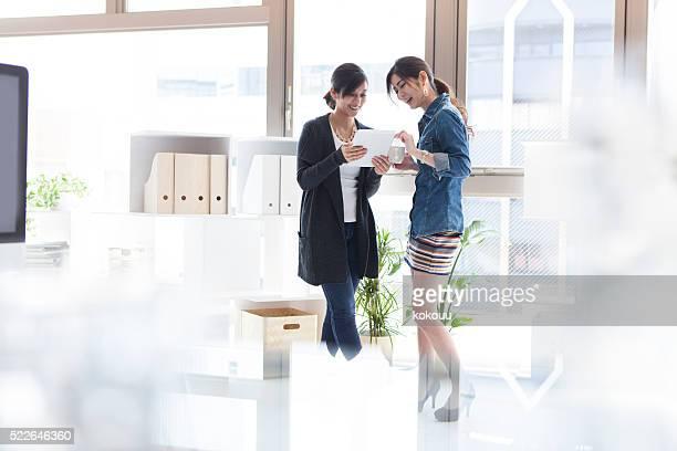 笑顔の女性がタブレットのビデオを見る