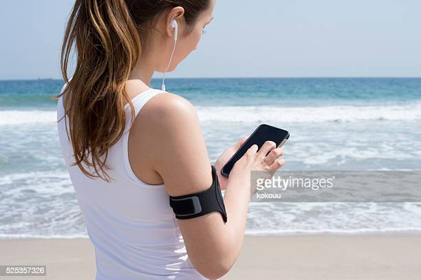 Women who are listening to music on smartphone at seaside