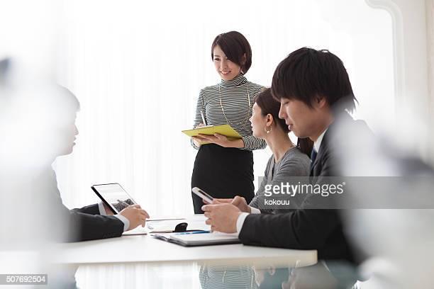 女性がタブレットを使用して、ミーティング中