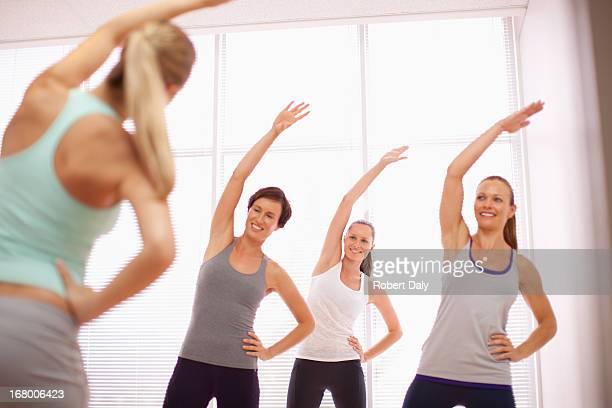Mujer con los brazos planteado en clase de ejercicio
