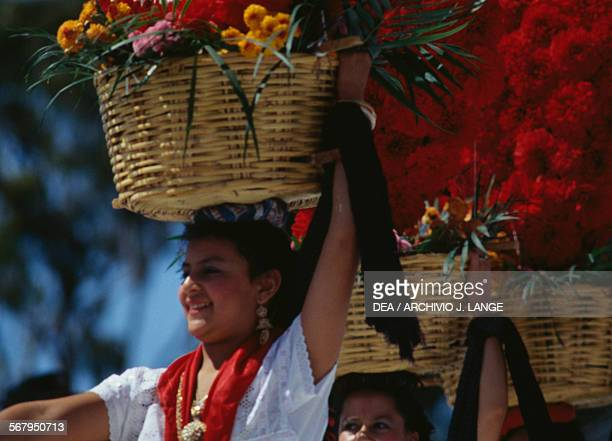 Women with baskets of flowers on their heads and wearing traditional costumes during the celebrations at the Guelaguetza festival Oaxaca Mexico