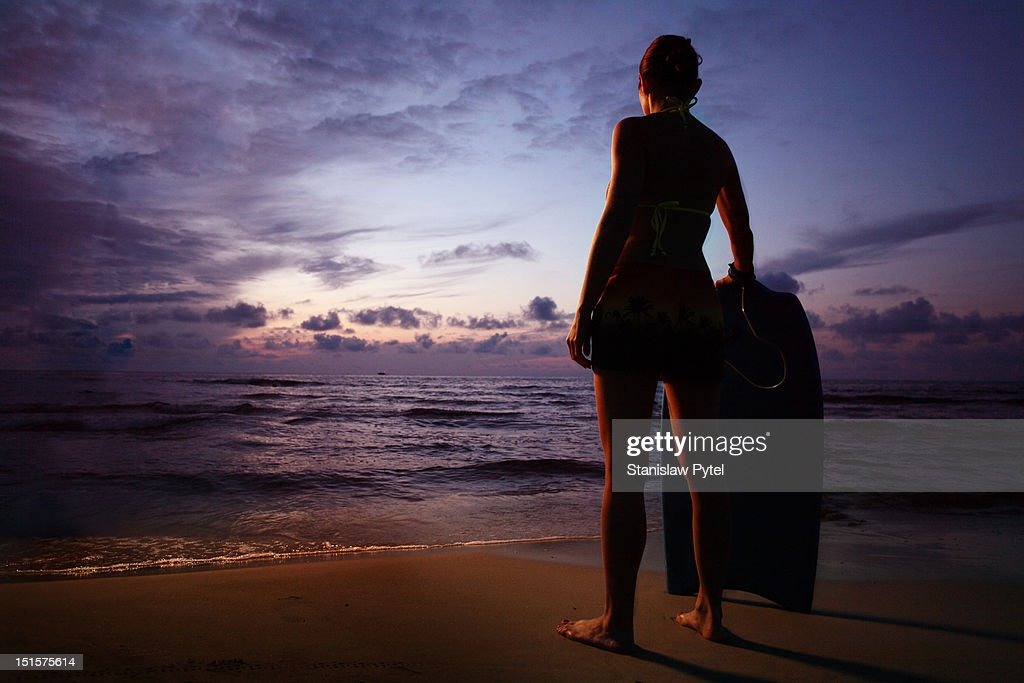 Women with bodyboard looking at sunset on sea : Stock Photo