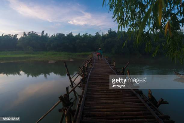 Women with bycicle cross the bamboo bridge at countryside Quang Ngai Vietnam in the early morning