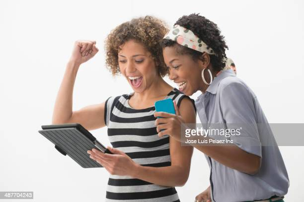 Women with digital tablet cheering