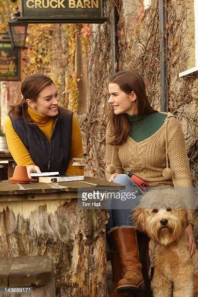 Femme avec un chien d'une bière au café