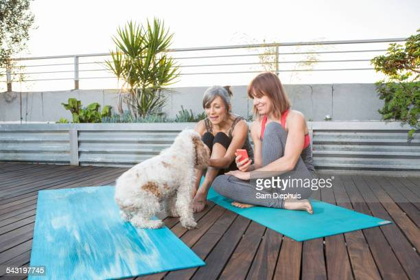 Women with dog using cell phone on exercise mat