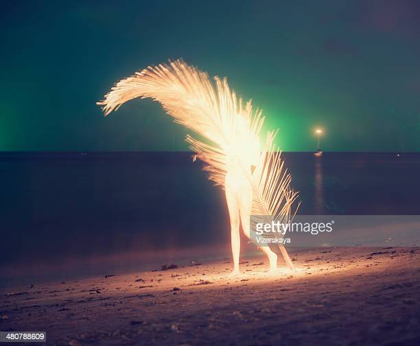 women with giant palm leaf at night