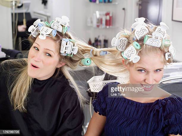 Women with hair tangled in rollers