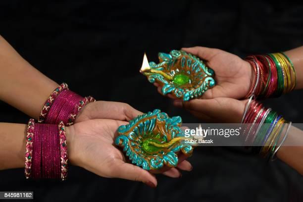 Women with lit earthen lamp at Diwali festival