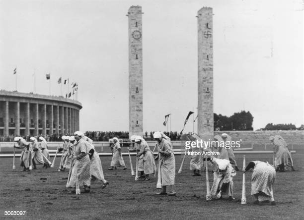 Women with mallets keeping the ground level during an interval in a polo match at the 1936 Olympics held in Berlin