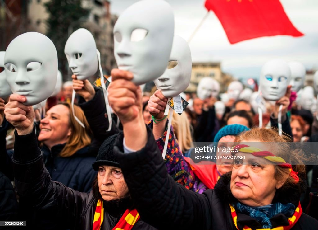 Women with masks participate in a demonstration against a deal between Social Democrats and the Albanian Democratic Union for Integration, for a law making Albanian the second official language, on March 13, 2017 in Skopje. Macedonian president Gjorge Ivanov, who has accused neighbouring Albania of trying to influence political developments across the border, referred to minority ethnic Albanian parties' decision to back opposition chief Zoran Zaev if he accepted their controversial demand to make Albanian an official language across Macedonia. / AFP PHOTO / Robert ATANASOVSKI
