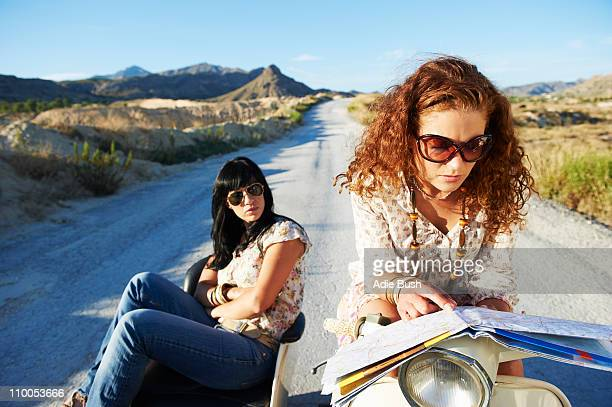Women with motorbike looking at map