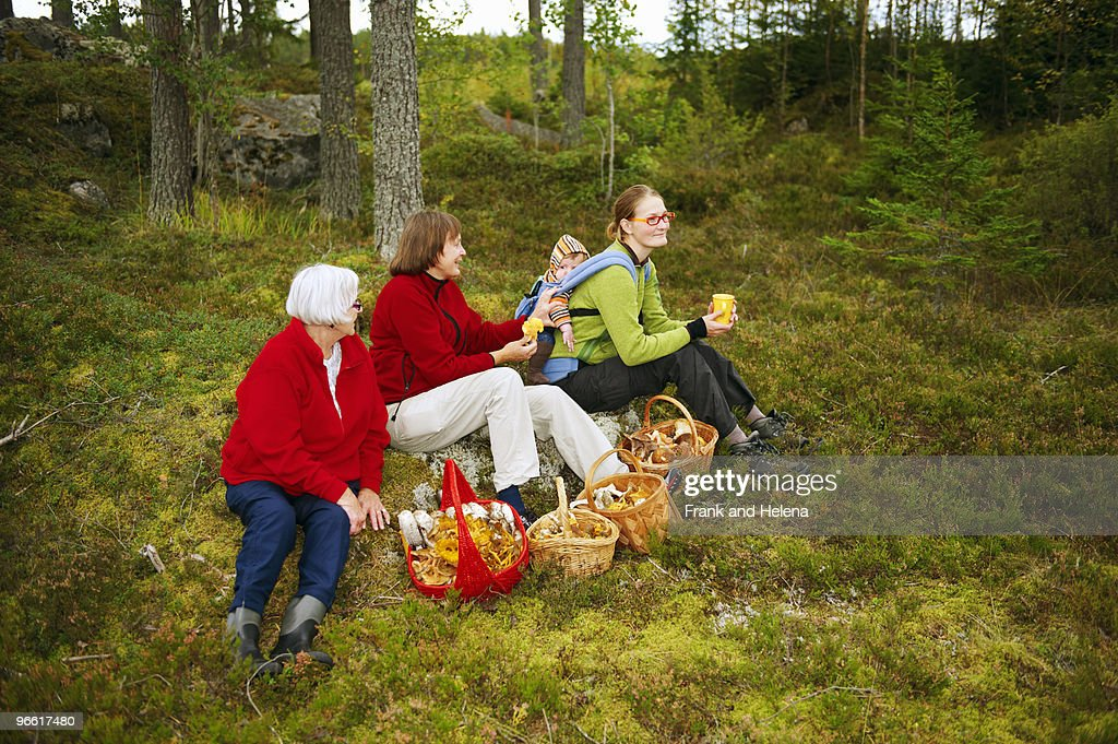 Women with mushroom baskets in forest : Stock Photo