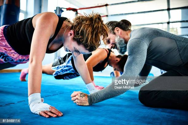 Women with personal trainer doing push ups in health club.