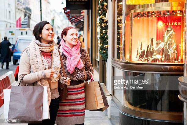 Women with shoopingbags looking at shopwindow.