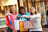 Women with shopping bags standing outside store