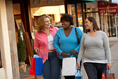 Women with shopping bags walking outside stores