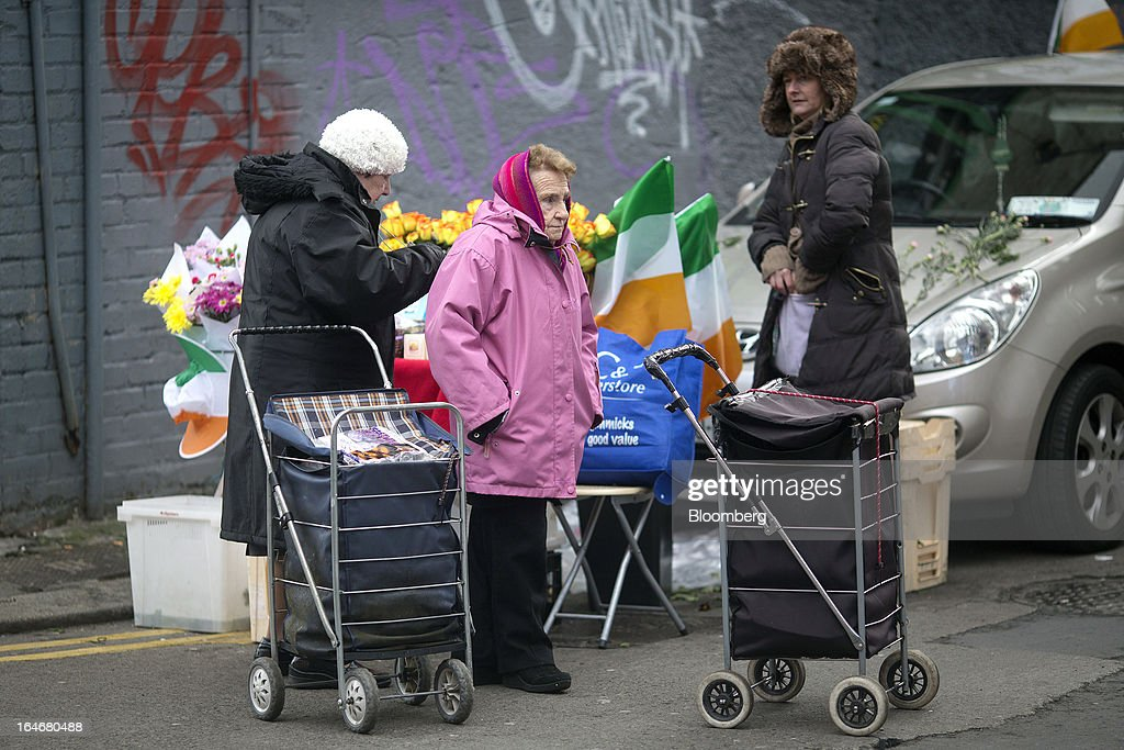 Women with shopping carts stand alongside a flower stall in Meath Street in Dublin, Ireland, on Saturday, March 16, 2013. Ireland's renewed competiveness makes it a beacon for the U.S. companies such as EBay, Google Inc. and Facebook Inc., which have expanded their operations in the country over the past two years. Photographer: Simon Dawson/Bloomberg via Getty Images