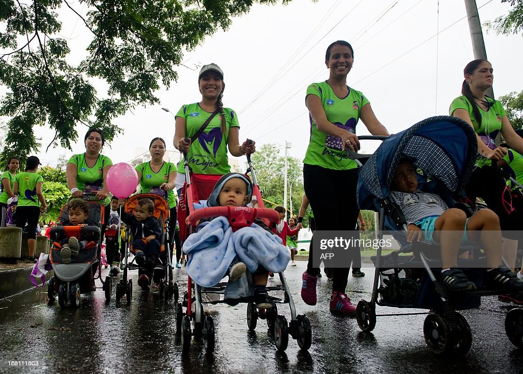 Women with their children run during the 'Race of Women' in Cali, Colombia, on May 5, 2013. Thousands of women, some with their children, took part in the race held in support of the fight against breast cancer and violence against women. AFP PHOTO/Luis ROBAYO