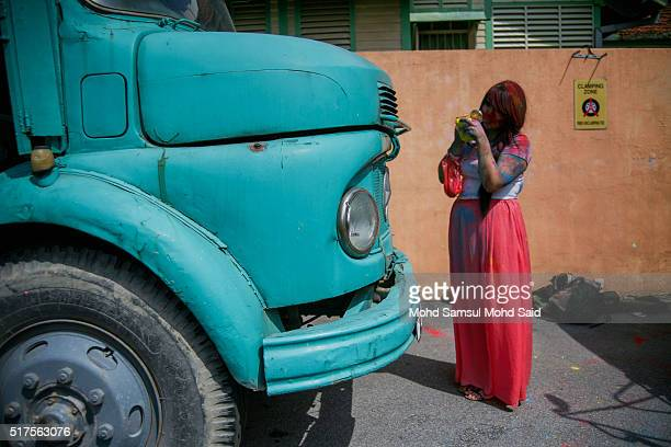 A women with their faces covered in coloured powder is seen stand near the lorry inside a temple during Holi festivals on March 26 2016 in Kuala...