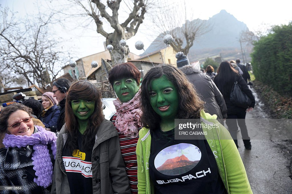 Women with their faces painted in green walk on December 21, 2012 in the French southwestern village of Bugarach, near the 1,231 meter high peak of Bugarach - one of the few places on Earth some believe will be spared when the world allegedly ends today according to claims regarding the ancient Mayan calendar. French authorities have pleaded with New Age fanatics, sightseers and media crews not to converge on the tiny village.