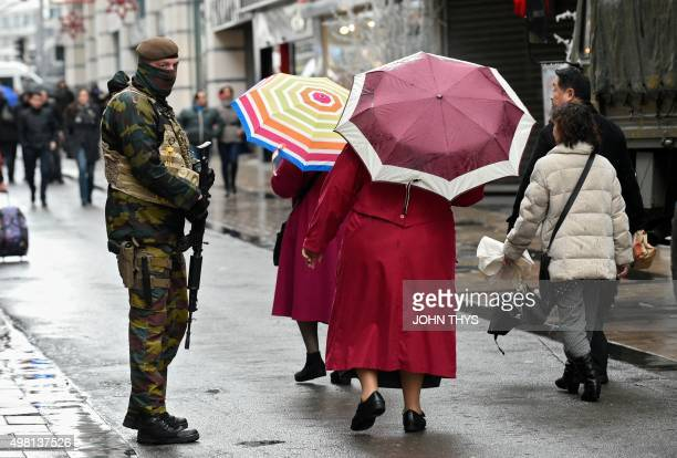 Women with umbrellas walk past a soldier patrolling the Rue Neuve pedestrian shopping street in Brussels on November 21 2015 All metro train stations...