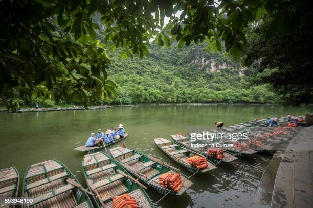 Women with Vietnamese hat sitting on rowing boats, waiting for transporting tourists for sightseeing adventures.