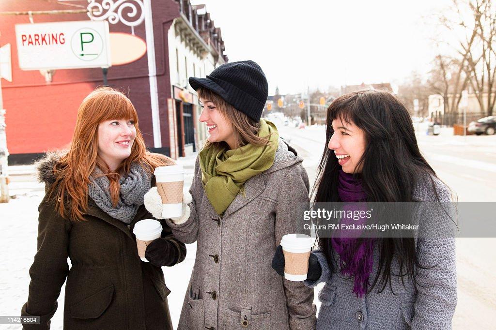 Women with warm drinks on snowy street : Stock Photo