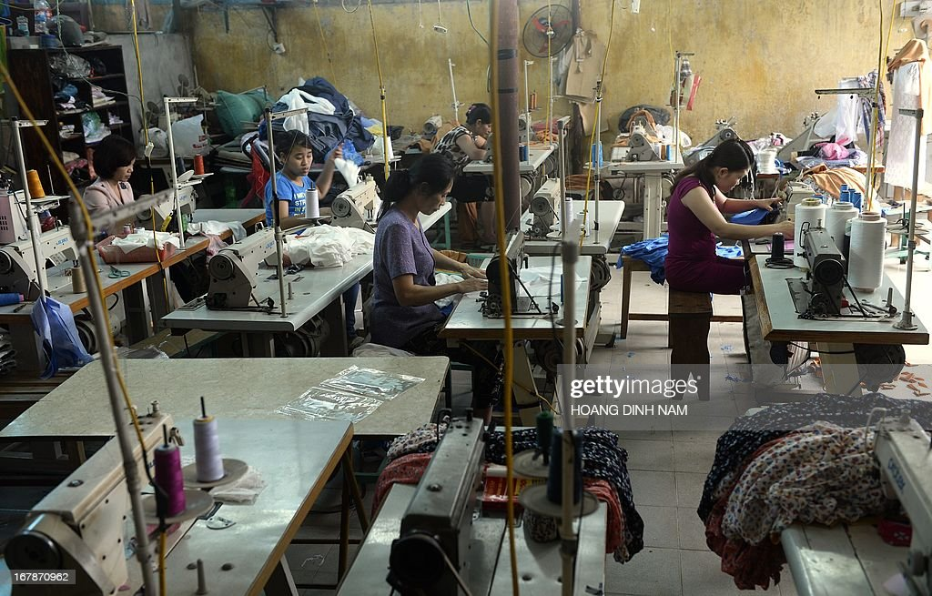 Women work at a small size garment workshop on the outskirds of Hanoi on May 2, 2013. From factory fires to slave labour, the growth of mass manufacturing in South East Asia has not been problem-free, but having shed its 'sweatshop' reputation, the region could have lessons for Bangladesh. AFP PHOTO/HOANG DINH Nam