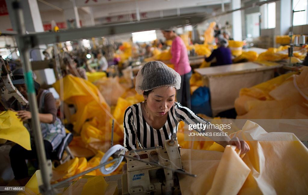 Women work on the CT1SL428 a protective suit for use in handling people infected with the Ebola virus in a sewing room of Lakeland Industries Inc in...