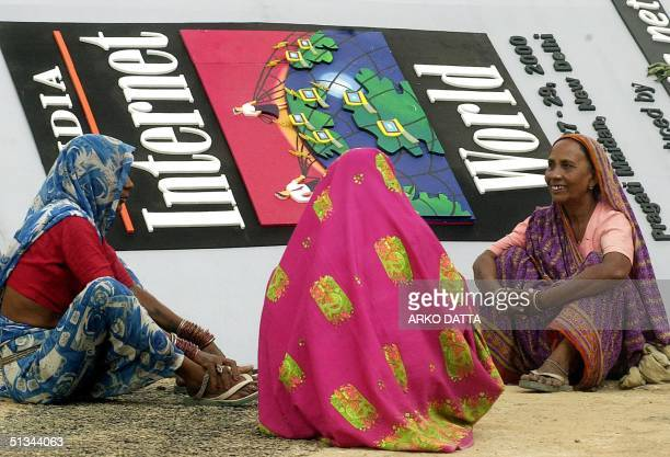 Women workers take a break in front of a banner during preparations 26 September 2000 for 'India Internet World Show 2000 ' India's largest Internet...