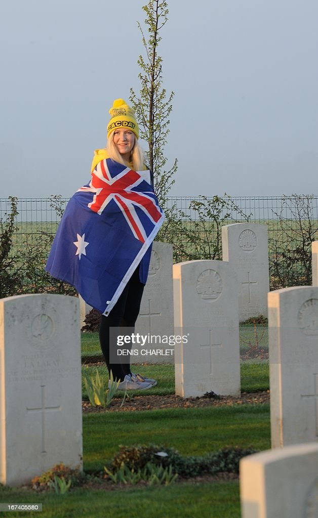 A women wrapped in an Australian flag walks past graves at the Australian War Memorial in the northern French city of Villers-Bretonneux, on April 25, 2013, as part of the Australian and New Zealand Army Corps (ANZAC) Day ceremony. Anzac Day commemorations are held each year on April 25 to mark the anniversary of the ill-fated landing of the Australian and New Zealand Army Corps (ANZAC) at Gallipoli in World War I.
